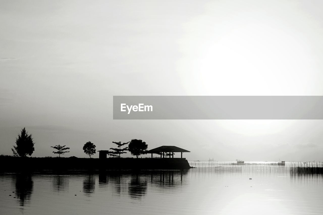 water, sky, architecture, built structure, waterfront, nature, reflection, beauty in nature, tranquility, tranquil scene, scenics - nature, tropical climate, no people, silhouette, sea, outdoors, building exterior, palm tree, tree
