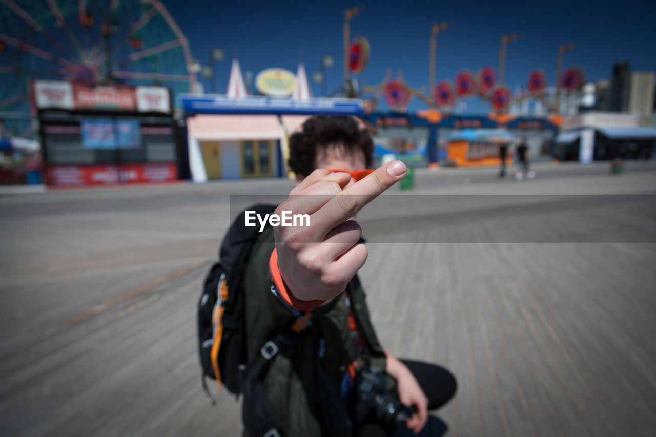 Man Showing Obscene Gesture While Standing At Coney Island