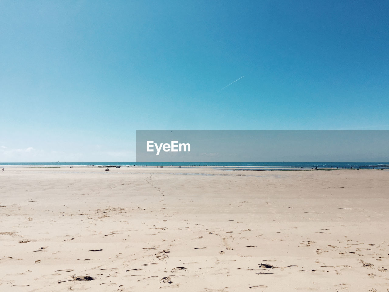 Scenic drone view of beach and ocean against blue sky