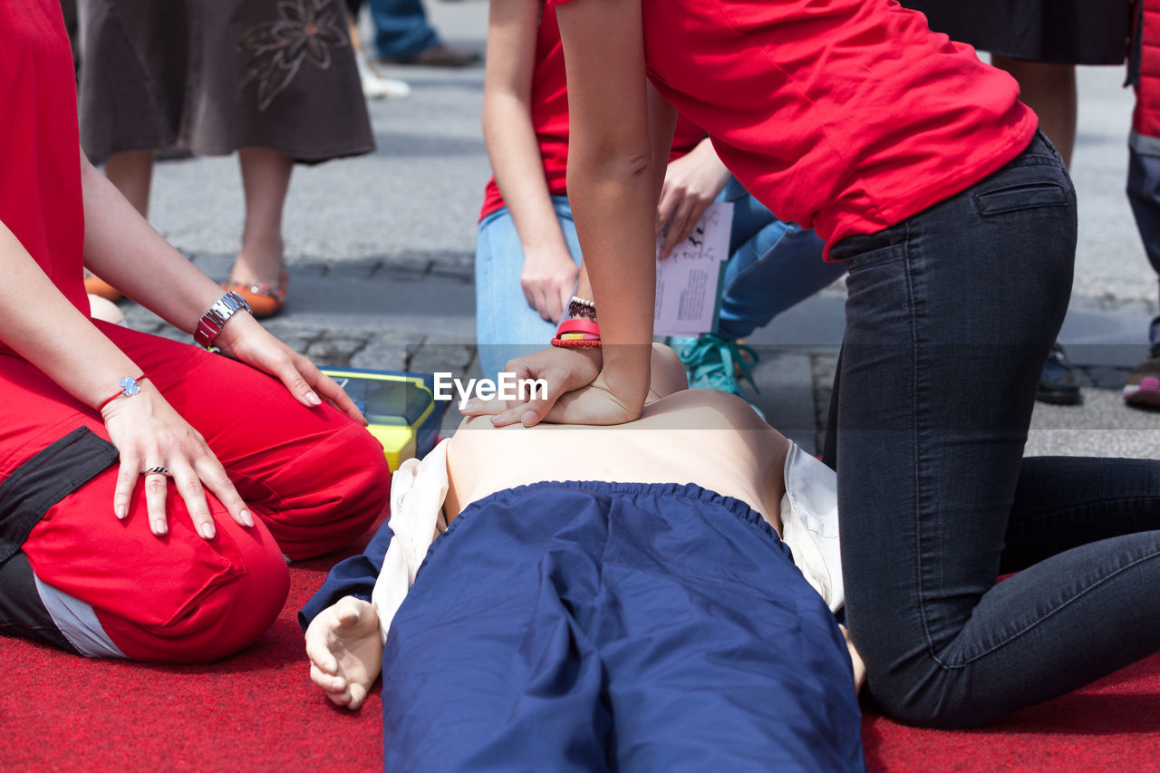 Midsection of people with cpr dummy during training