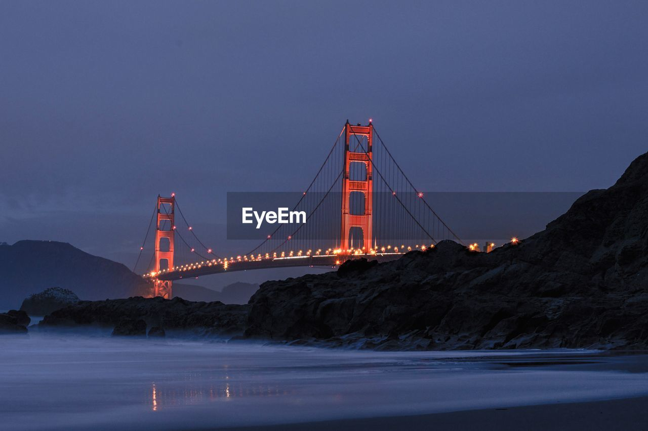 Illuminated golden gate bridge against cloudy sky at dusk