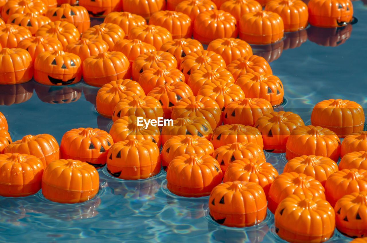Mini plastic pumpkins float in a small kiddie pool, each with a number on the bottom for a prize