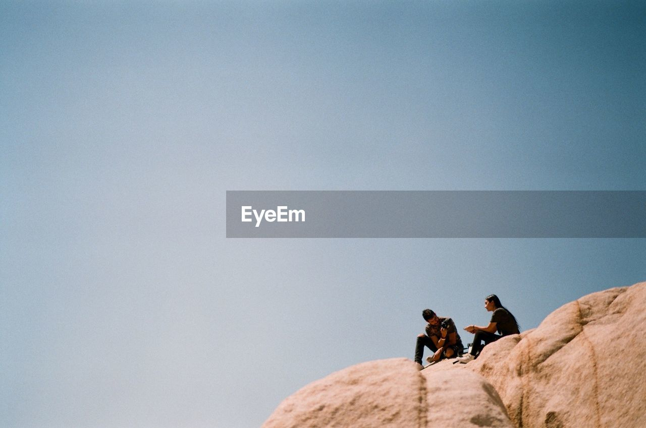 Man Photographing Woman On Rock Against Sky