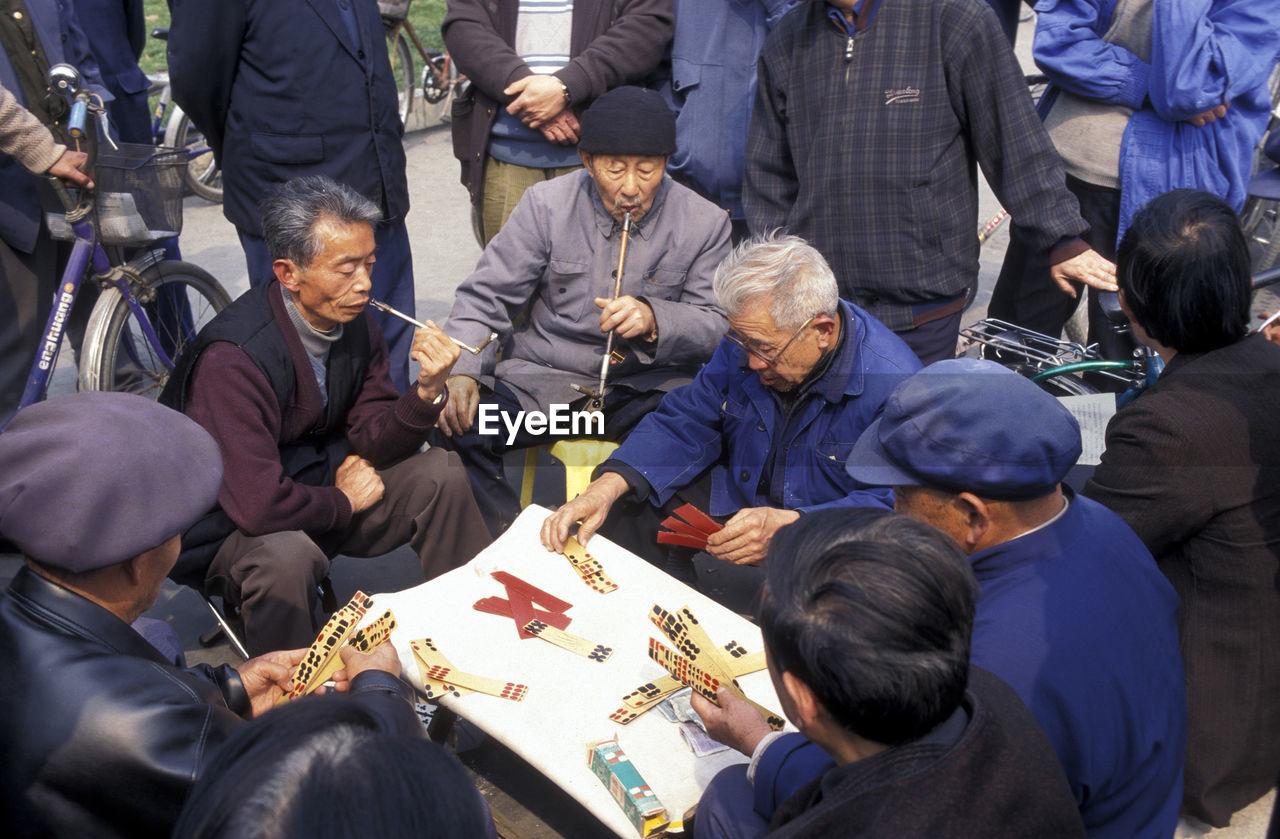 Senior Men Playing Cards On Street