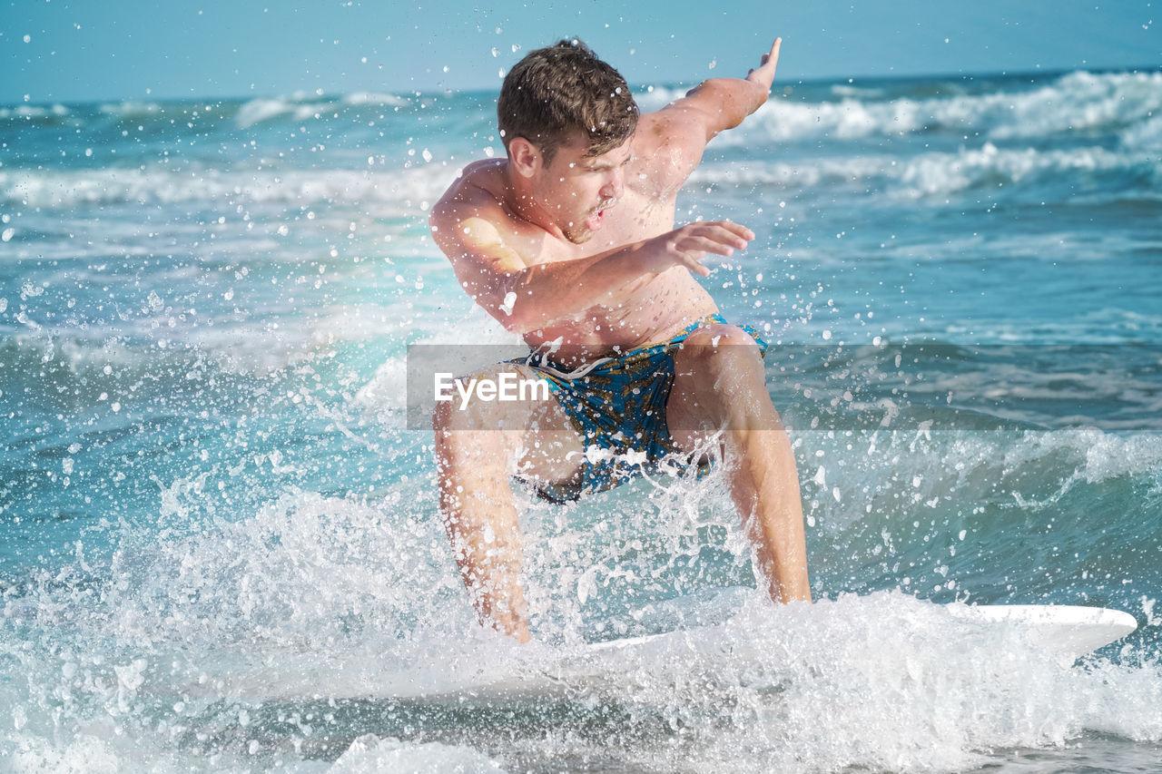 Shirtless Man Surfing In Sea