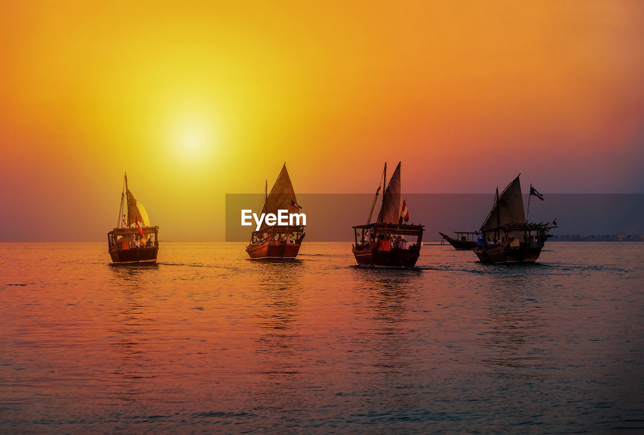 transportation, sunset, nautical vessel, water, mode of transportation, sky, sea, orange color, waterfront, scenics - nature, beauty in nature, nature, idyllic, tranquility, tranquil scene, sun, silhouette, no people, non-urban scene, outdoors, sailboat, fishing industry