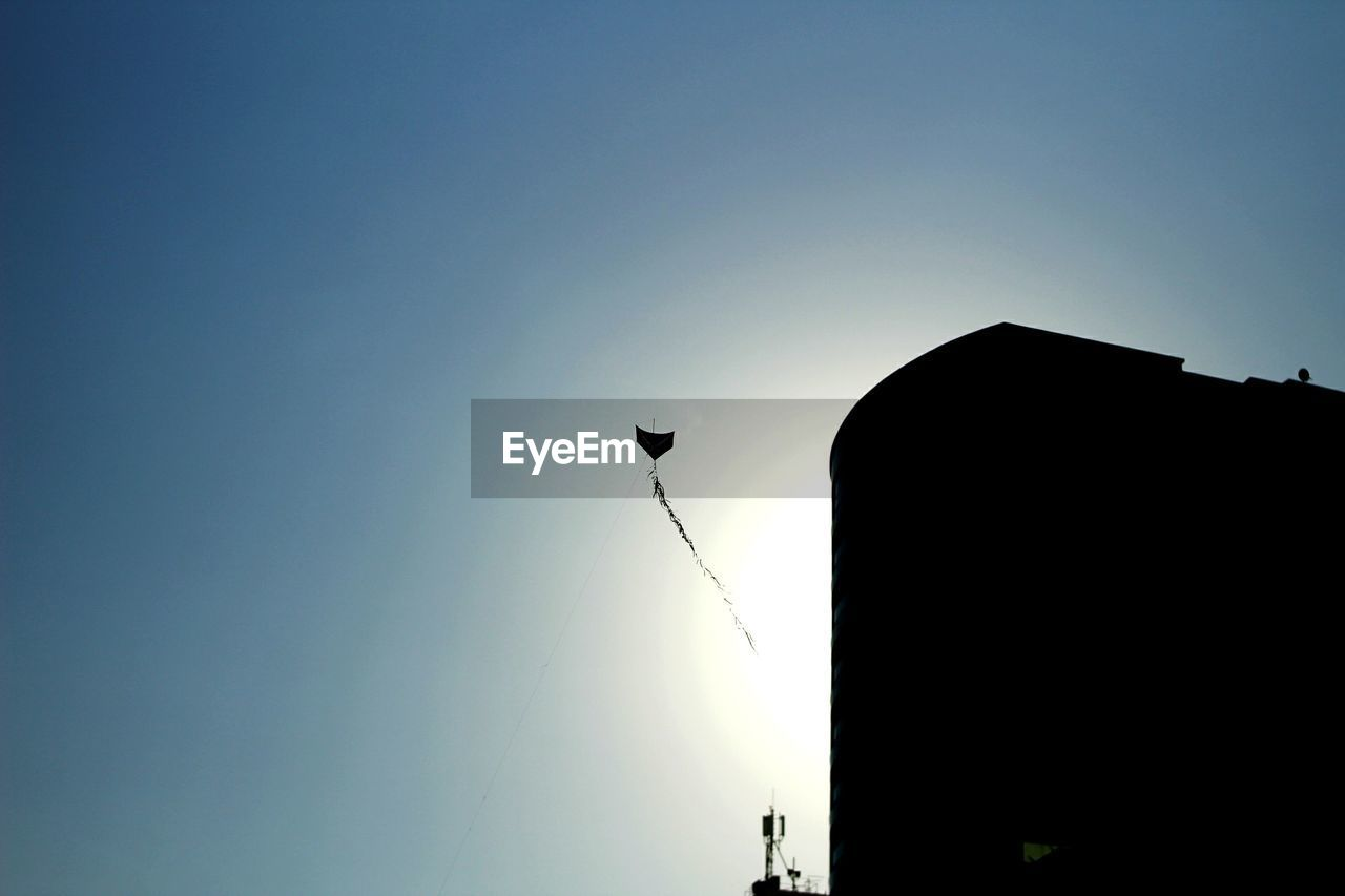 silhouette, low angle view, copy space, clear sky, outdoors, no people, sunset, sky, day, architecture, nature, building exterior, bird, animal themes