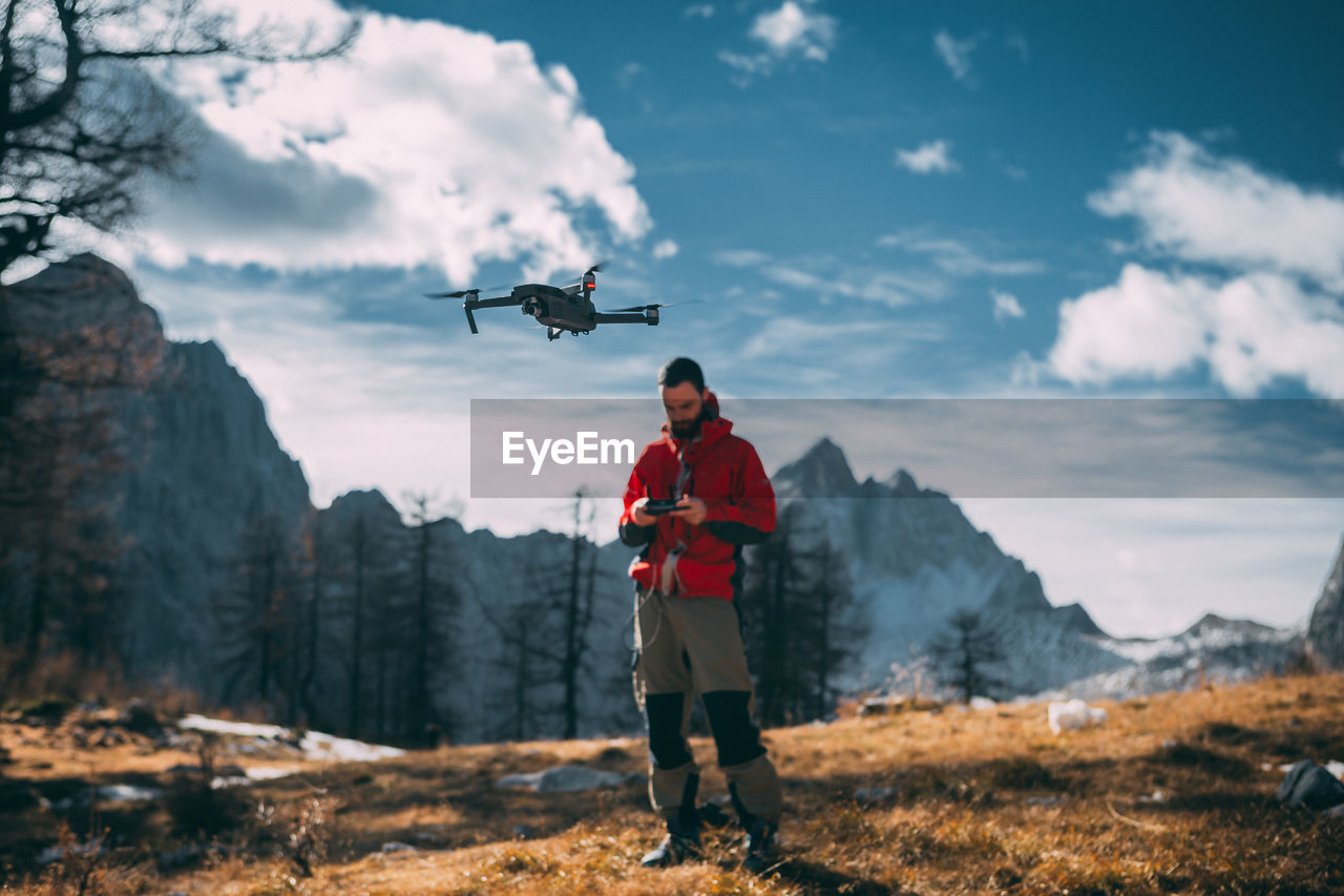 Man flying drone against mountains