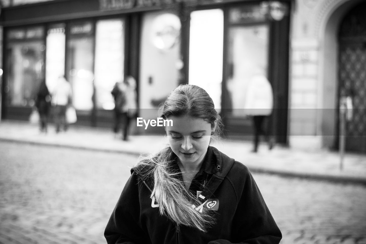 focus on foreground, one person, front view, young adult, lifestyles, real people, portrait, young women, smiling, incidental people, women, leisure activity, waist up, headshot, standing, casual clothing, architecture, day, beautiful woman, warm clothing, hairstyle, teenager