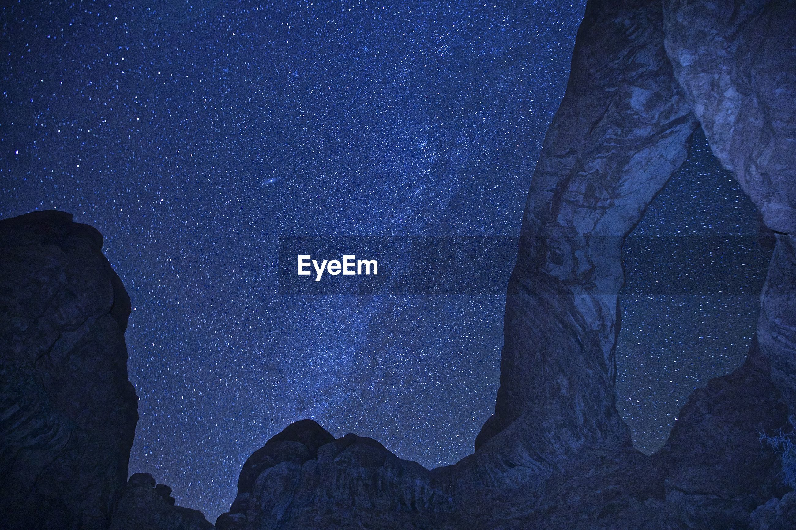 Low angle view of rock formation against star field at night