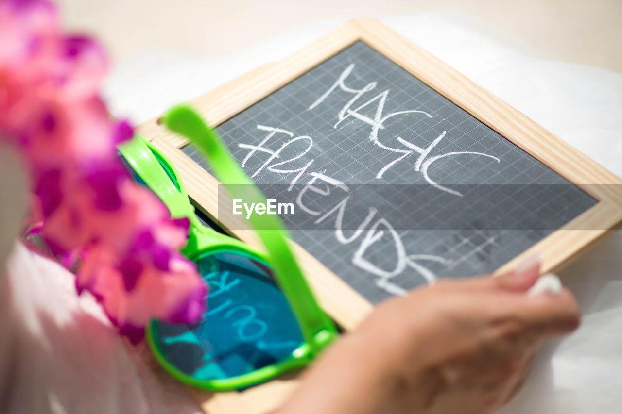 Cropped image of bride holding slate with text