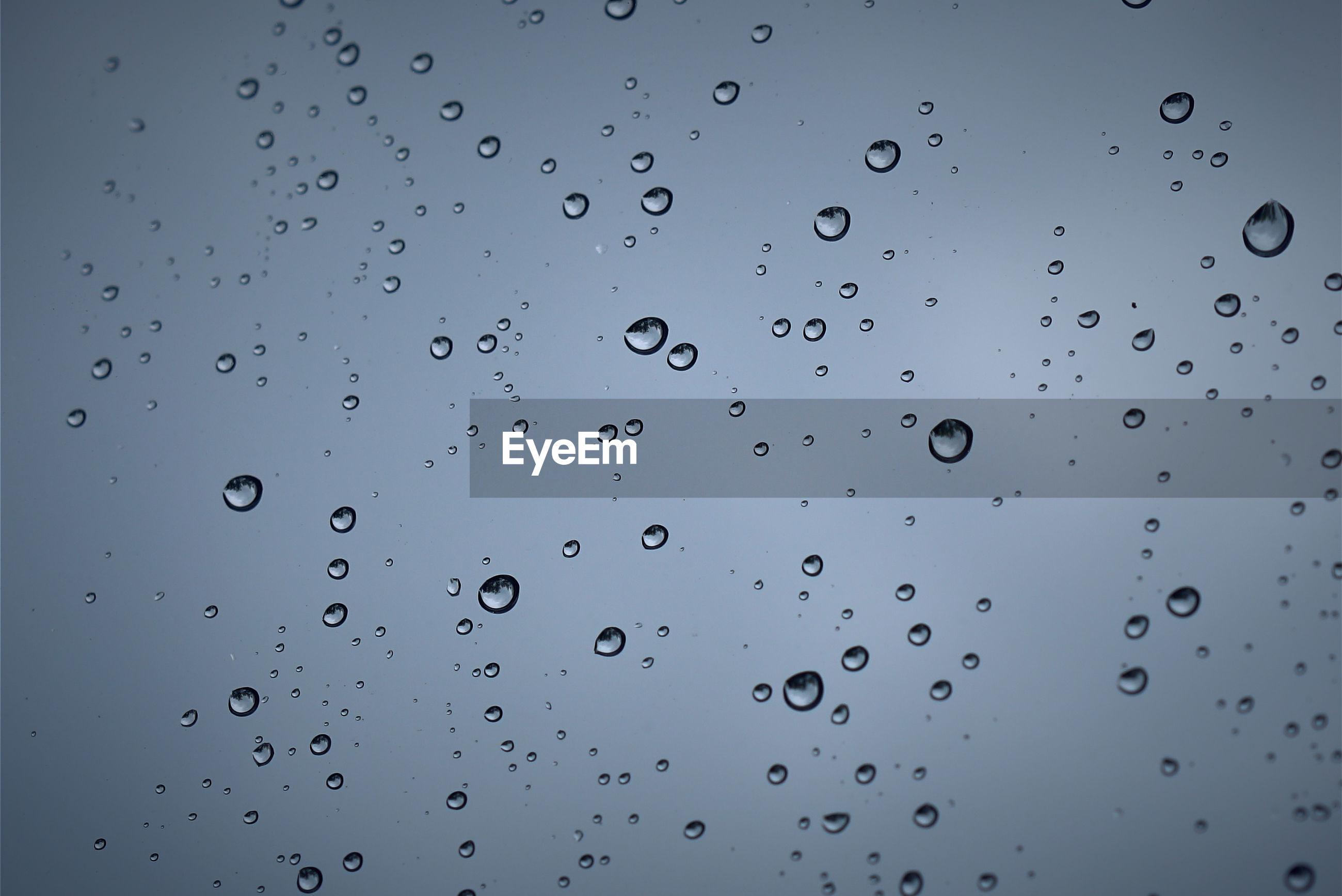 Full frame shot of water drops on window against sky