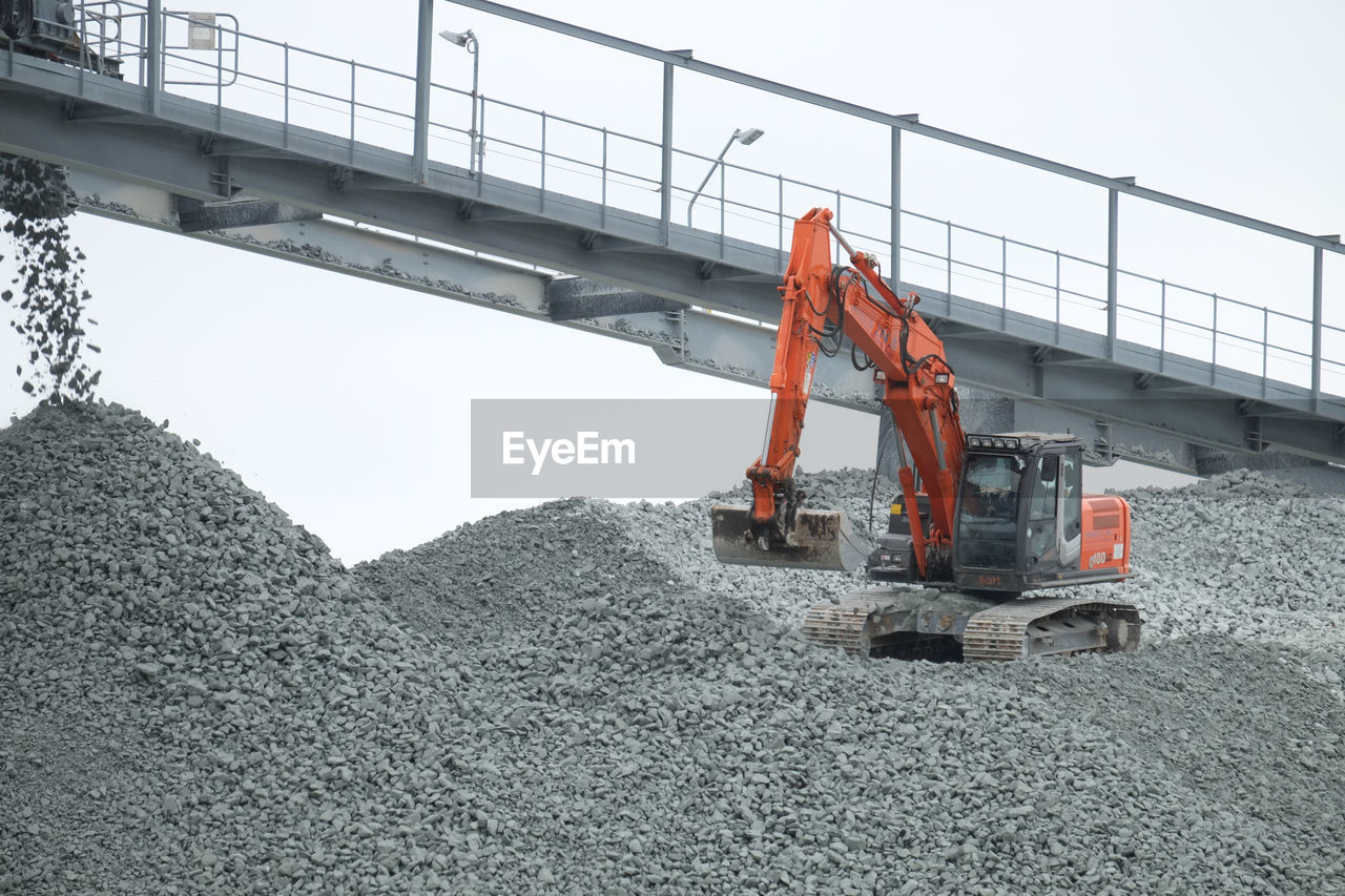 machinery, industry, transportation, construction industry, construction machinery, sky, construction site, earth mover, development, nature, day, heap, land vehicle, bulldozer, outdoors, equipment, mode of transportation, land, mining, crane - construction machinery, industrial equipment