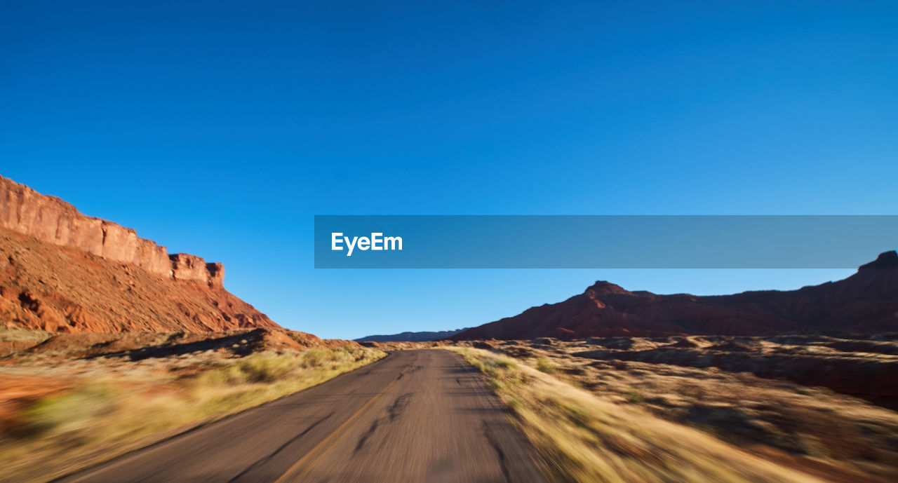 sky, mountain, clear sky, blue, scenics - nature, road, landscape, the way forward, copy space, transportation, beauty in nature, nature, environment, tranquil scene, non-urban scene, direction, no people, rock, day, travel, climate, mountain range, arid climate, outdoors, formation