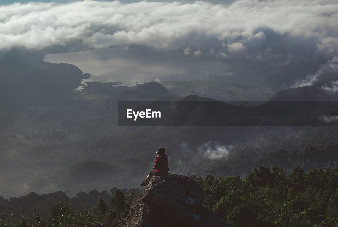 Hiker sitting on rock against mountain range