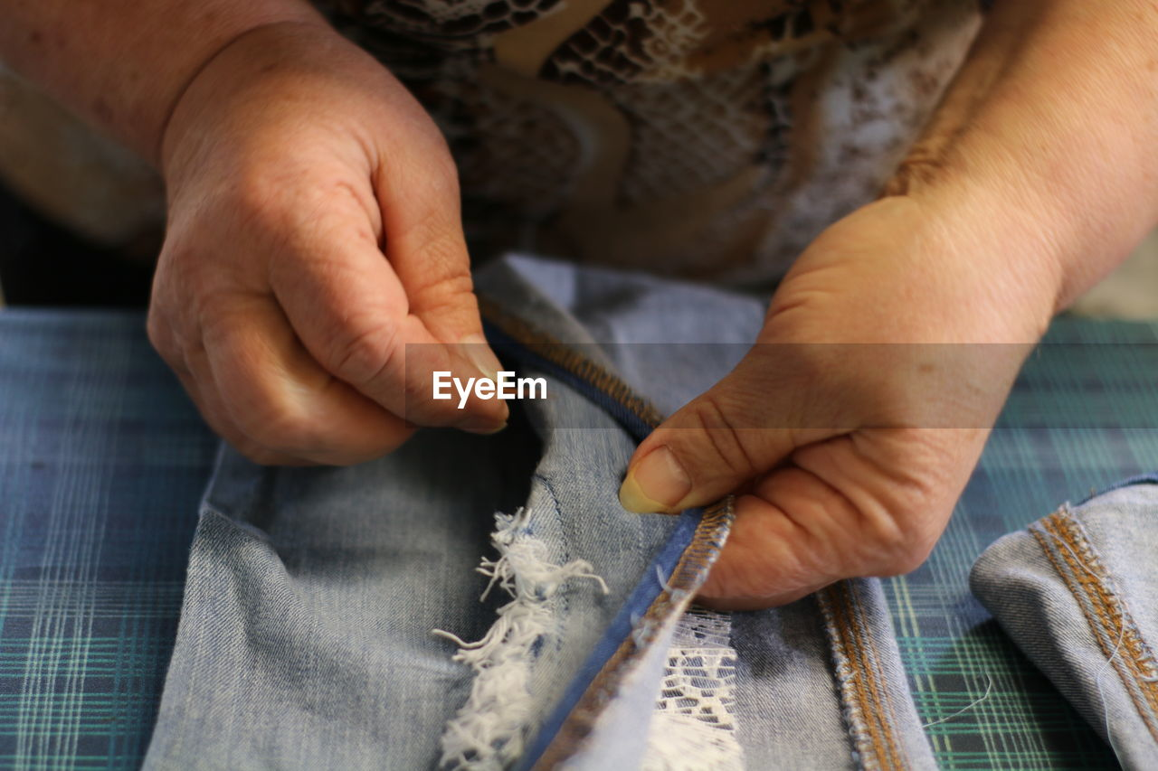 Midsection Of Woman Stitching Fabric At Table