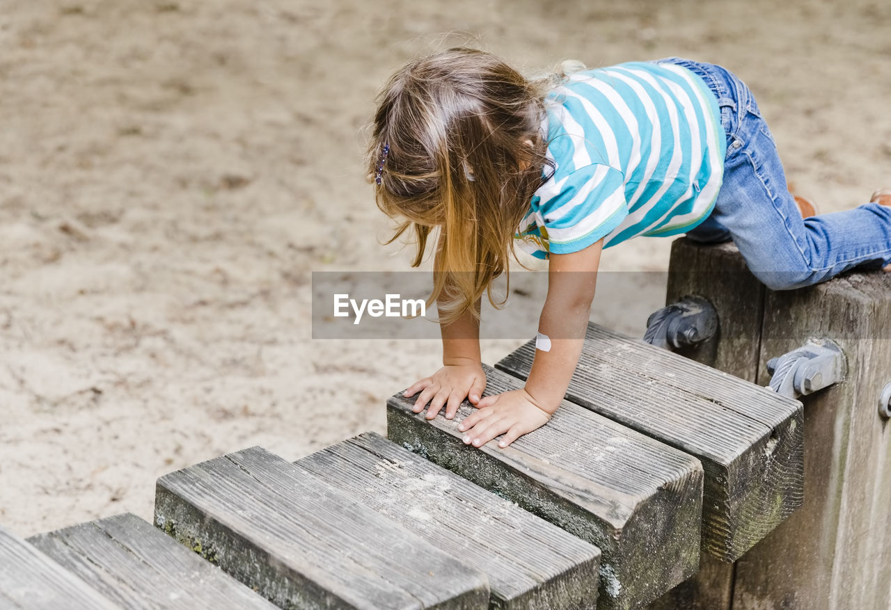 HIGH ANGLE VIEW OF CHILD STANDING BY WOOD