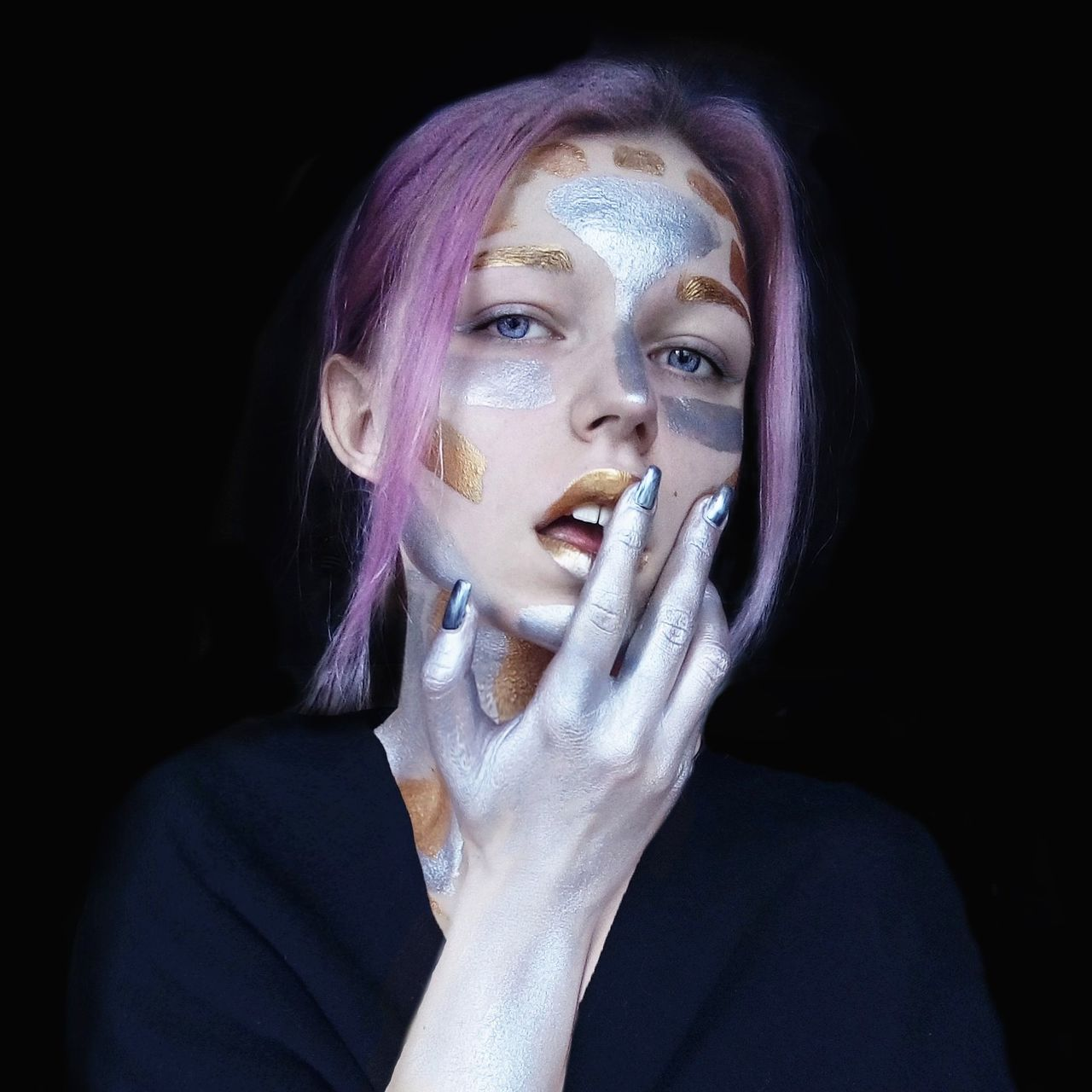 Close-up portrait of young woman with face paint against black background