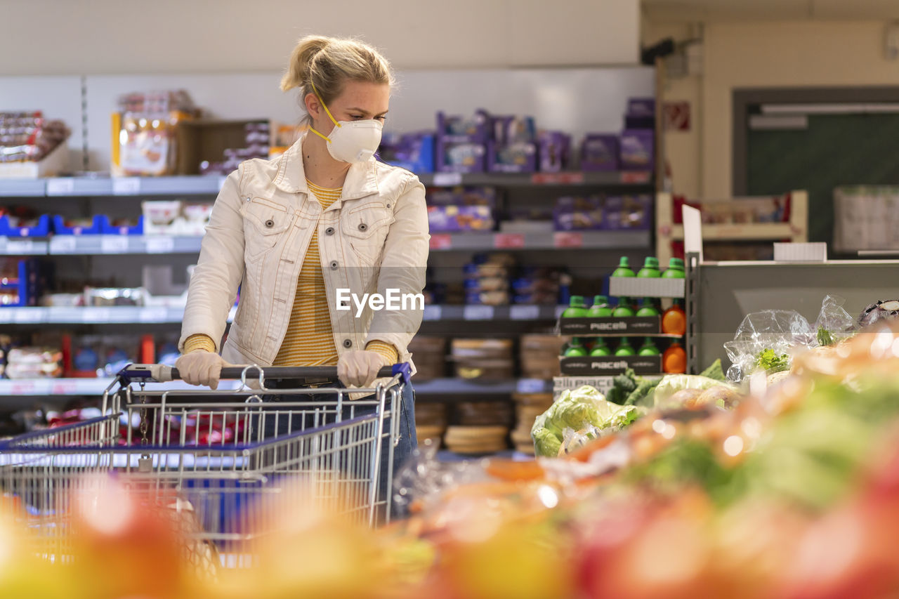 FULL LENGTH OF WOMAN STANDING BY STORE IN SHOP