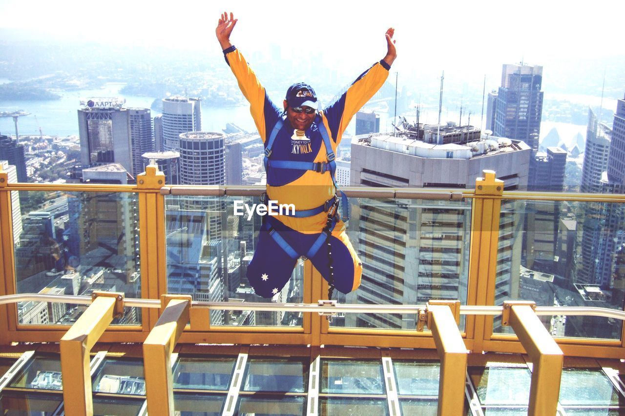 Man With Arms Outstretched Jumping Over Building Terrace By Cityscape Against Sky