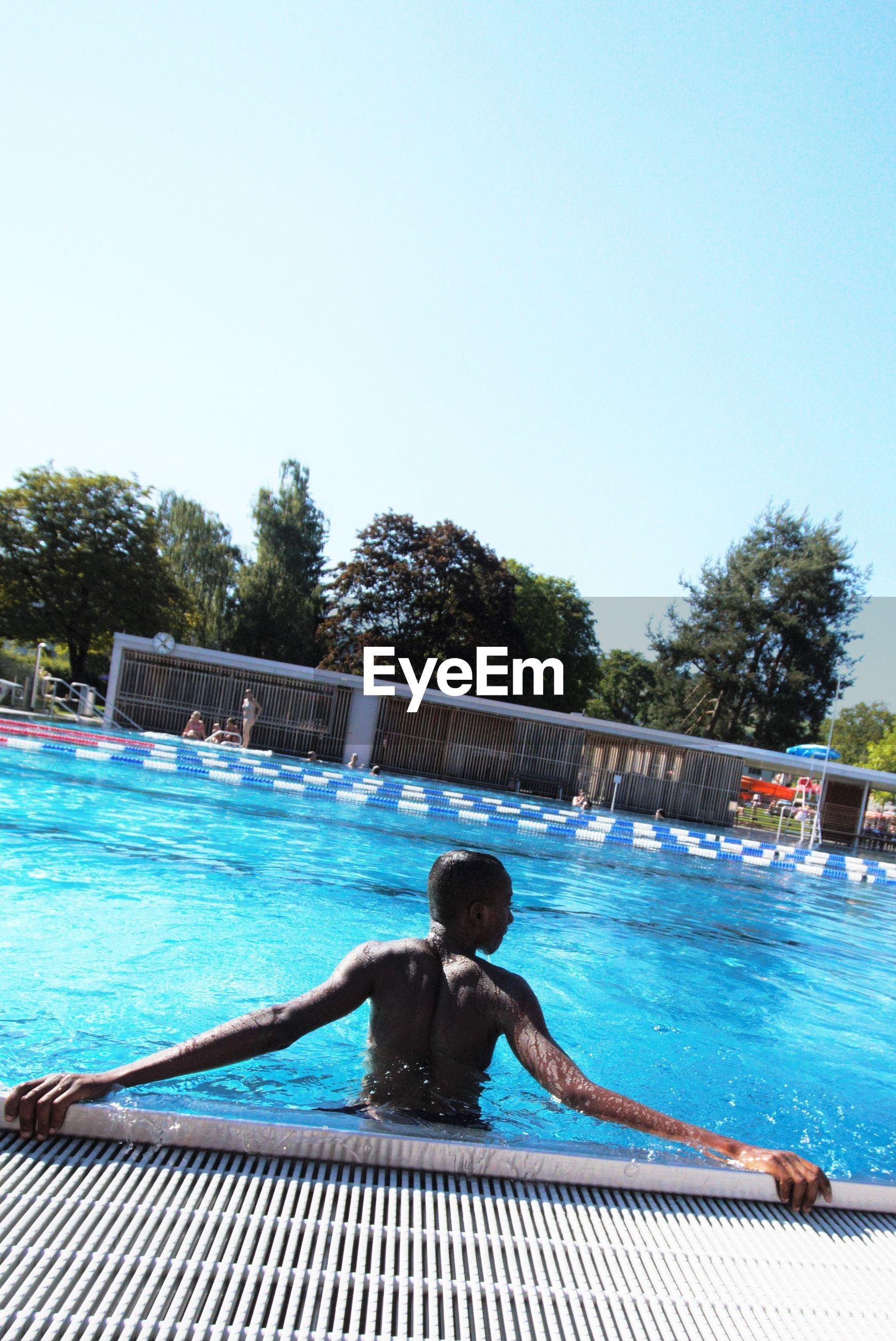 Rear view of shirtless man standing in swimming pool against clear sky