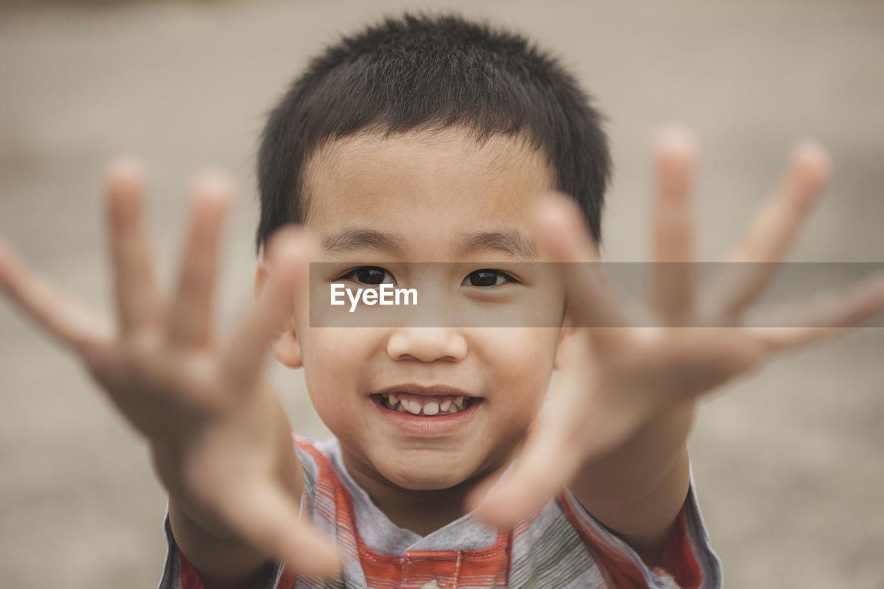 Close-up portrait of innocent boy gesturing