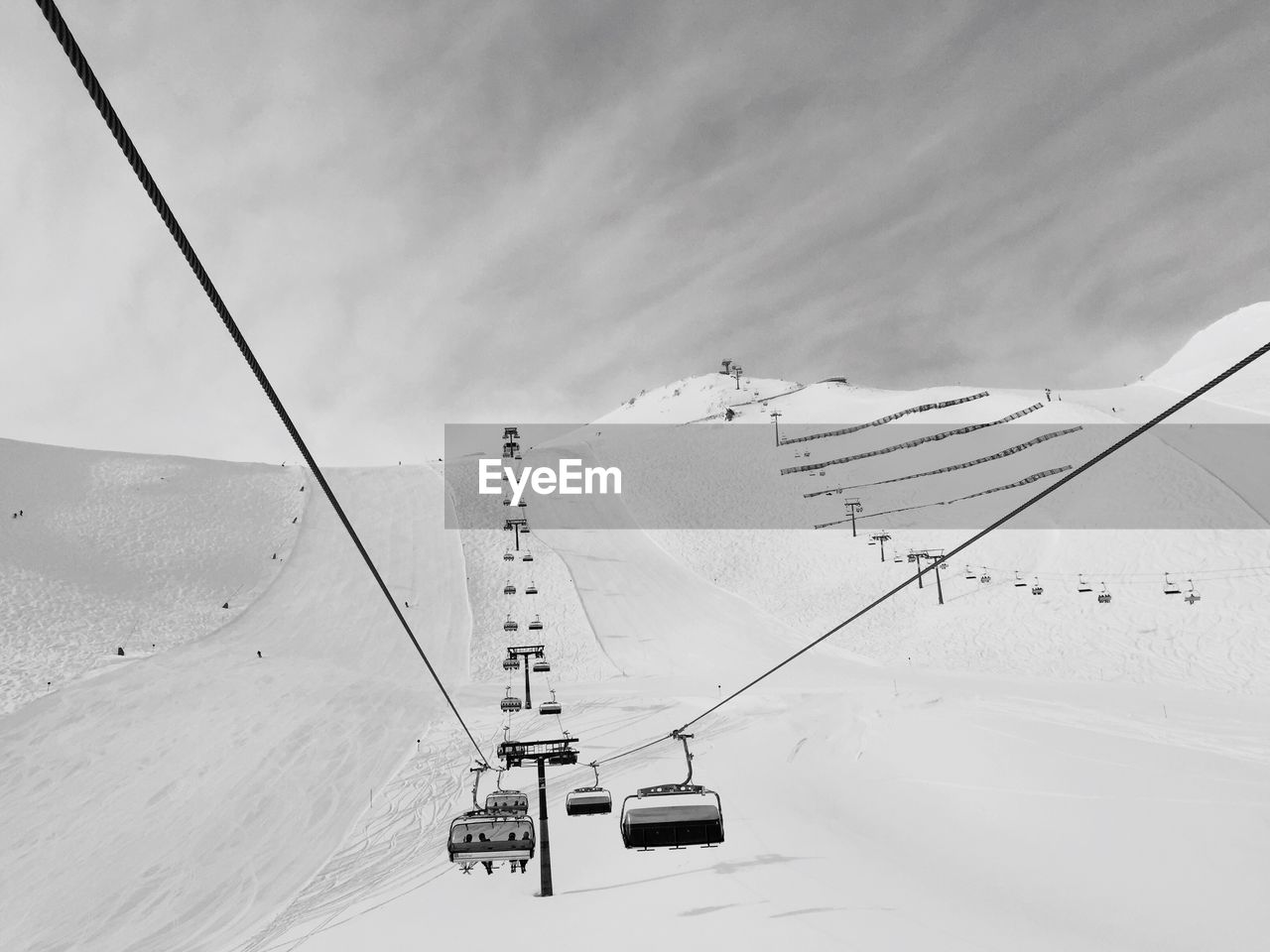 Ski Lift And Snow Covered Mountain Against Sky