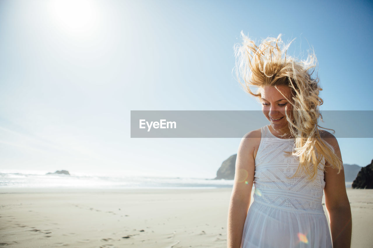 Smiling Young Woman Standing At Beach Against Clear Sky