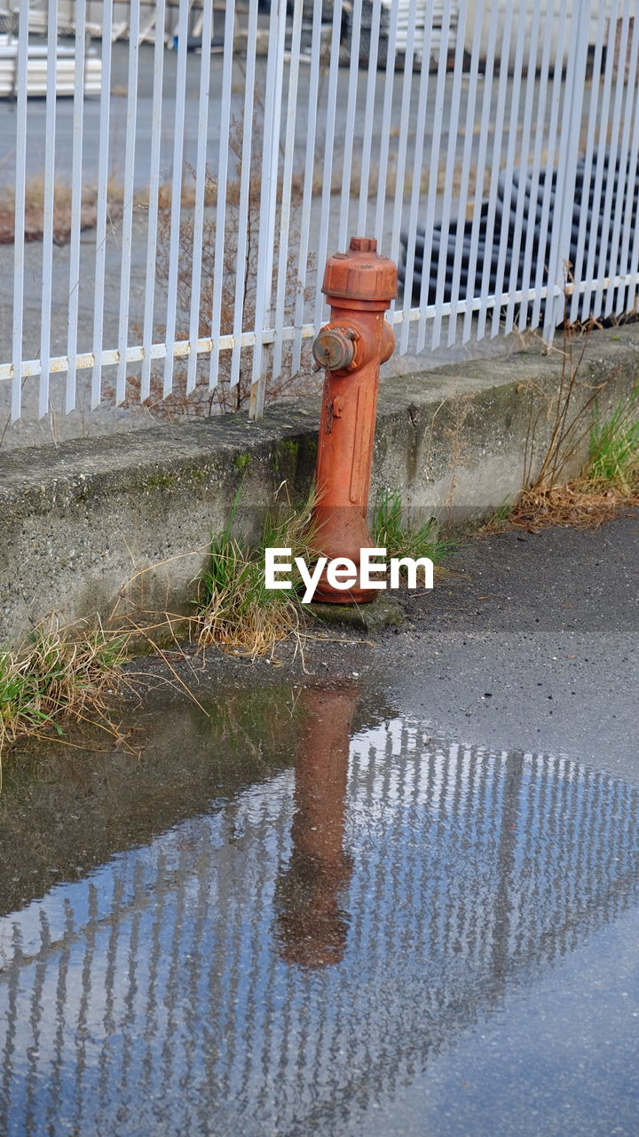 water, protection, safety, high angle view, puddle, no people, day, reflection, outdoors, sewer, fire hydrant