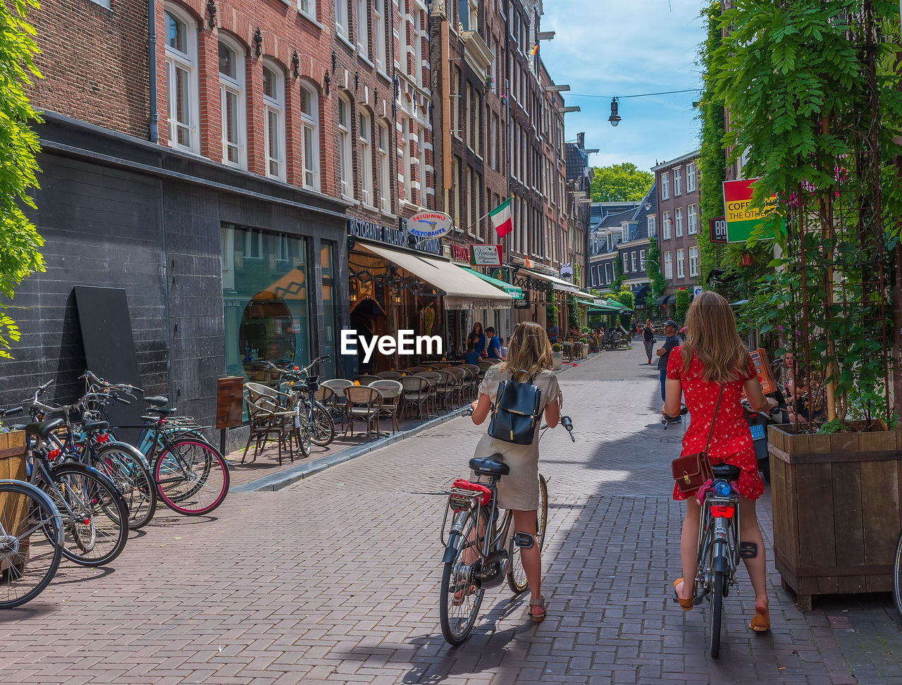 building exterior, bicycle, transportation, architecture, city, mode of transportation, real people, built structure, land vehicle, street, group of people, lifestyles, women, people, day, building, leisure activity, adult, incidental people, men, outdoors, riding