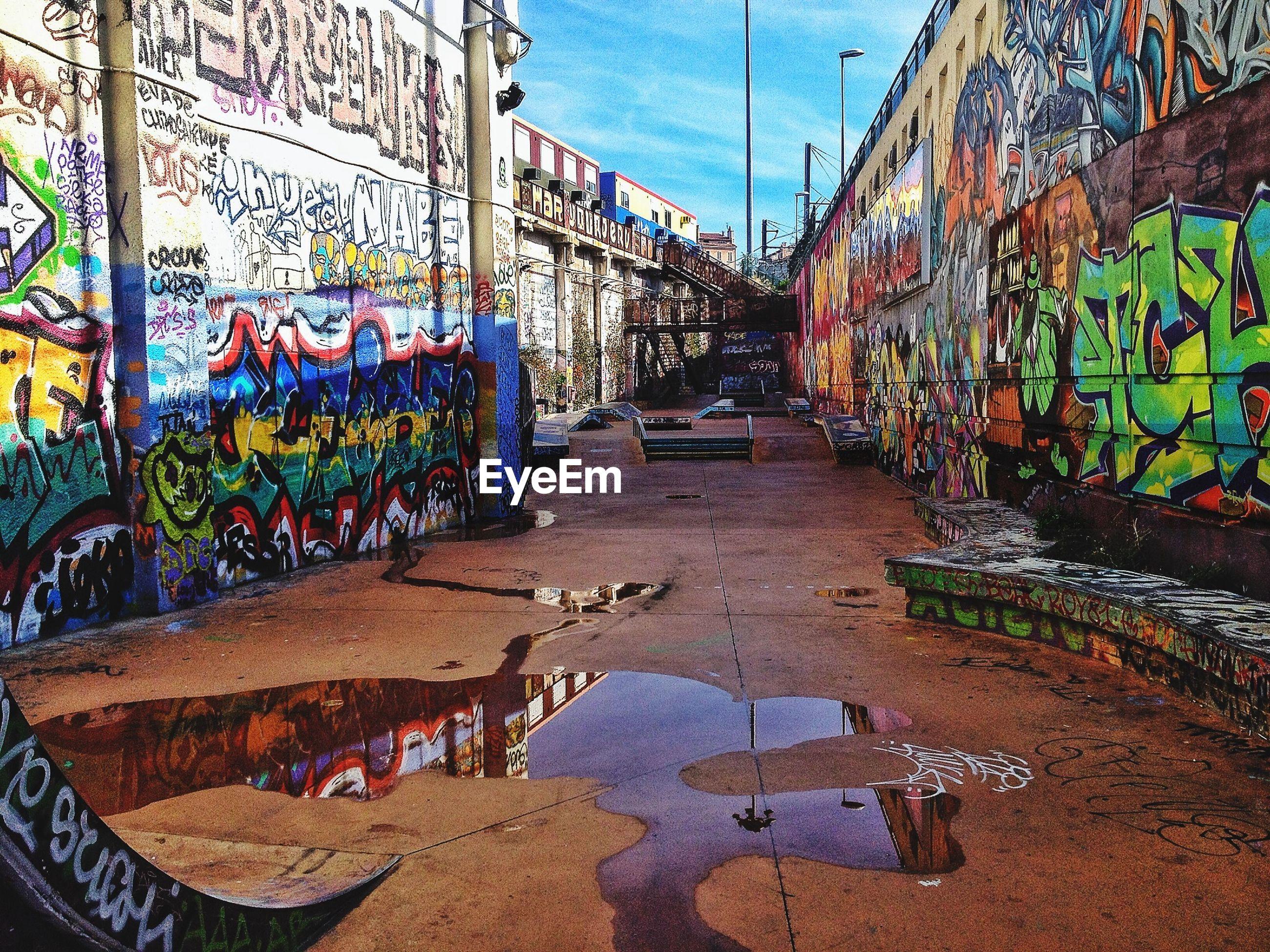 Walkway amidst graffiti walls
