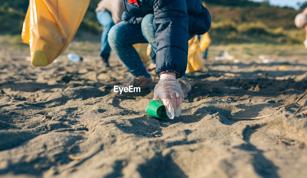 Low section of girl picking garbage at beach