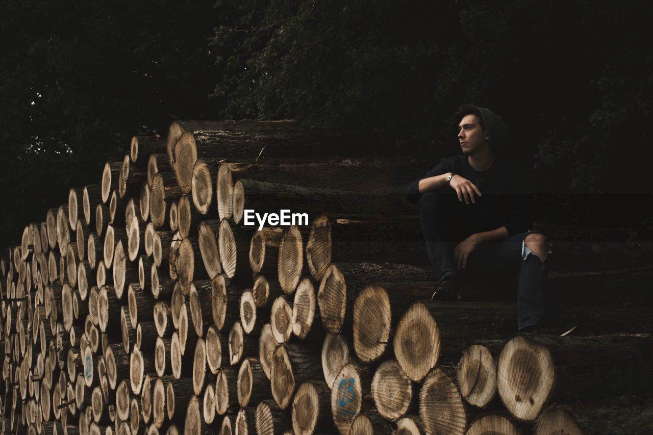 Full Length Of Young Woman Sitting On Logs