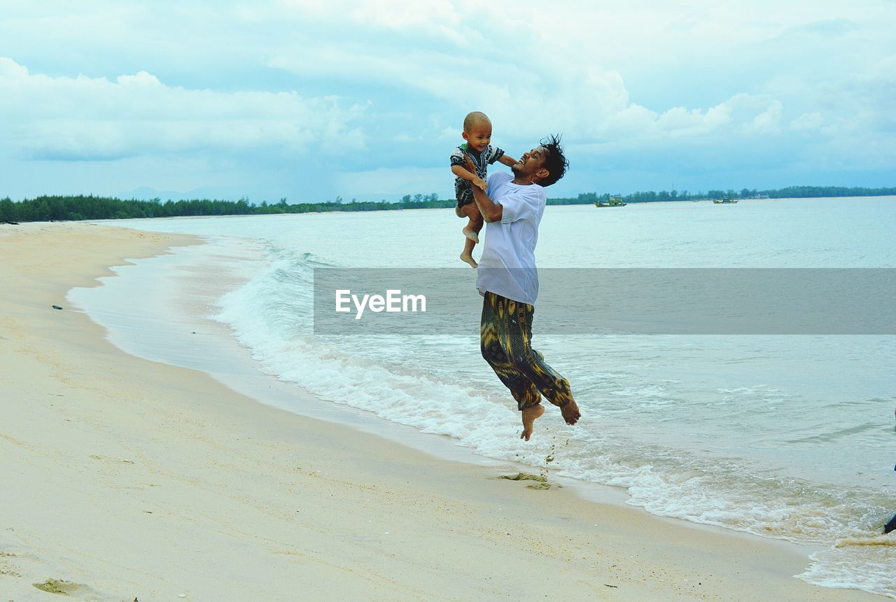Full Length Of Father With Son Jumping On Shore At Beach