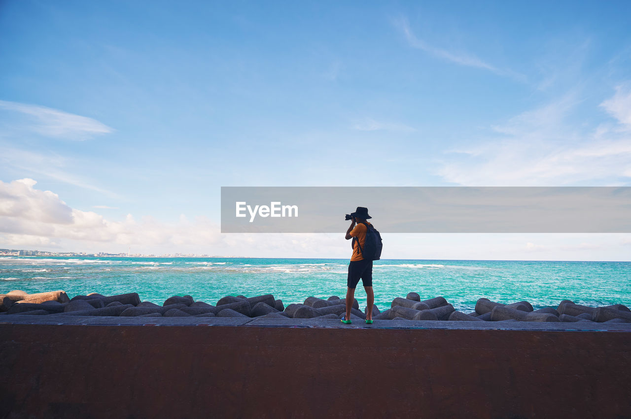 sky, sea, water, cloud - sky, horizon over water, horizon, scenics - nature, lifestyles, real people, one person, leisure activity, beauty in nature, rock, rock - object, solid, men, standing, day, land, outdoors