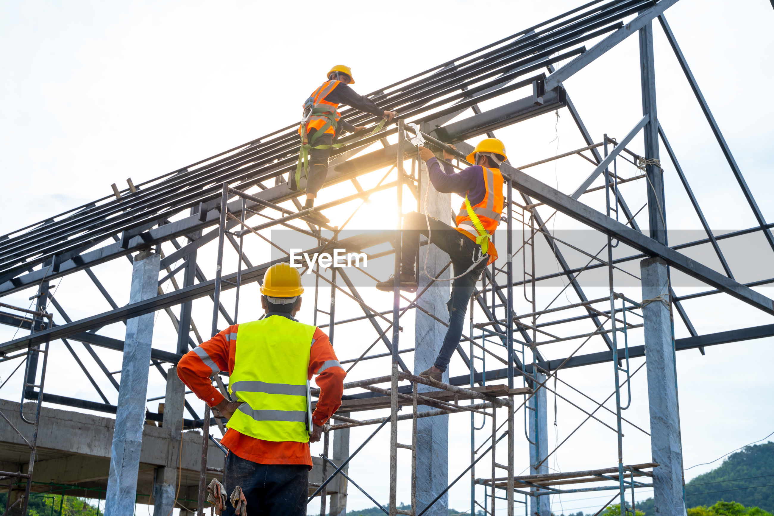 LOW ANGLE VIEW OF CONSTRUCTION WORKER AT CRANE