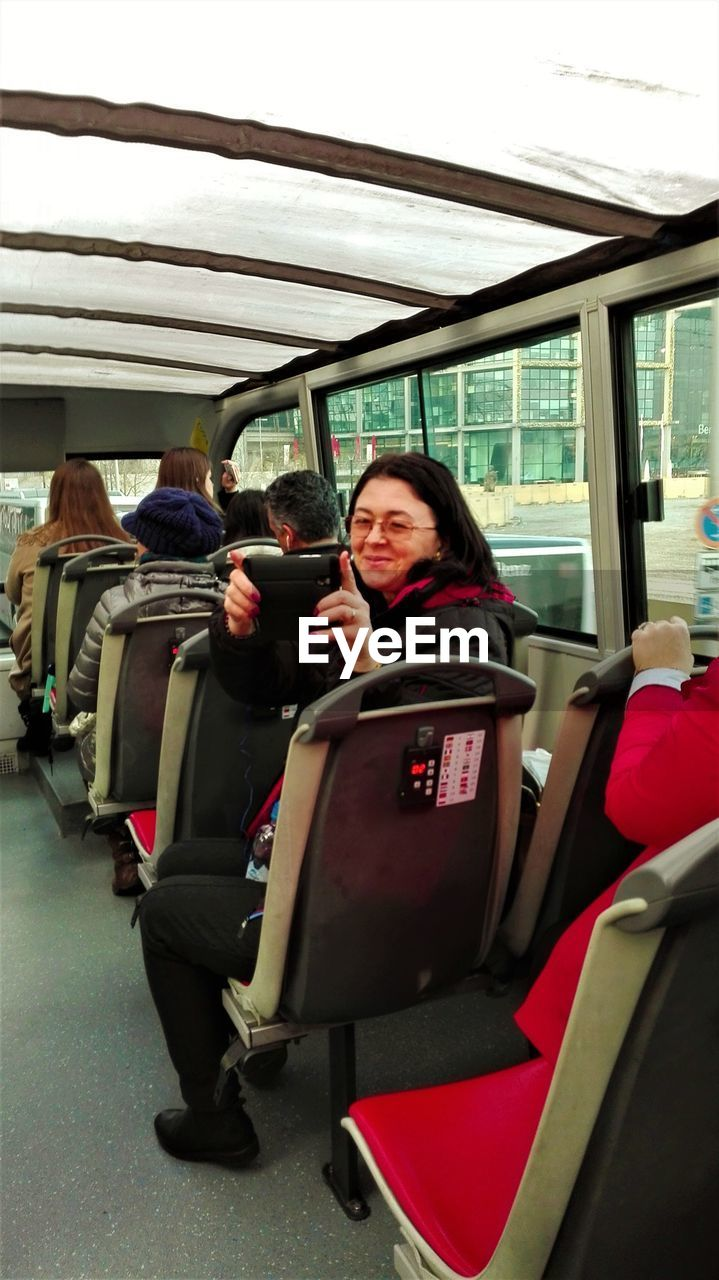 real people, sitting, transportation, lifestyles, public transportation, one person, vehicle seat, young adult, wireless technology, young women, day, warm clothing, adult, people