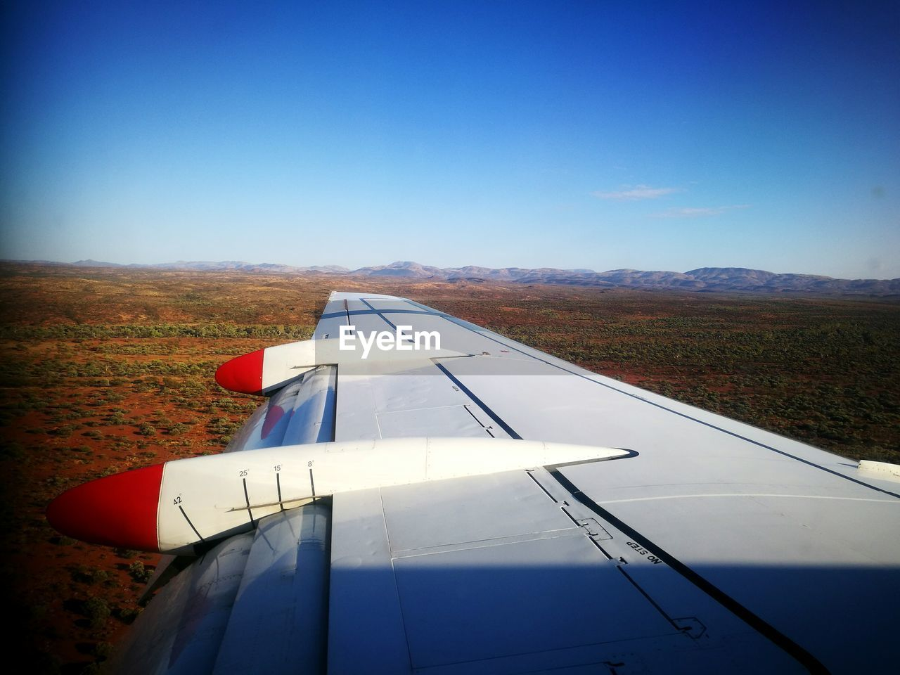 airplane, transportation, air vehicle, journey, mode of transport, travel, no people, blue, day, aircraft wing, flying, airplane wing, outdoors, nature, clear sky, landscape, sky, beauty in nature, close-up