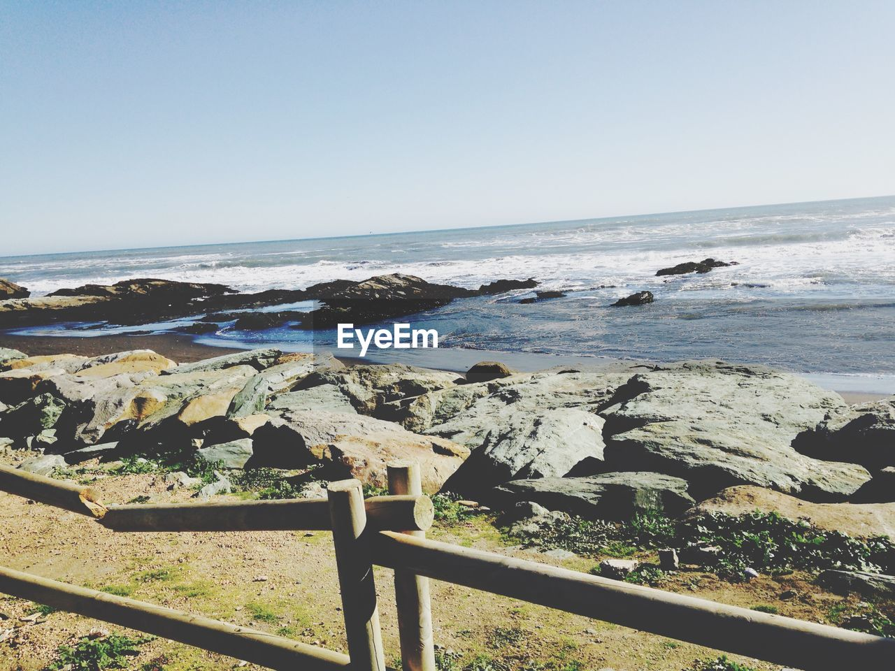 Scenic view of sea with broken railing on foreground against clear sky