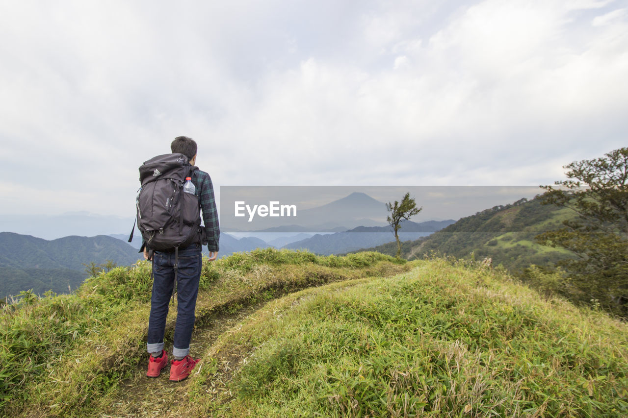 mountain, hiking, backpack, cloud - sky, beauty in nature, nature, adventure, mountain range, real people, sky, full length, scenics, casual clothing, hiker, tranquil scene, rear view, day, men, grass, leisure activity, tranquility, one person, lifestyles, green color, outdoors, standing, vacations, landscape, people