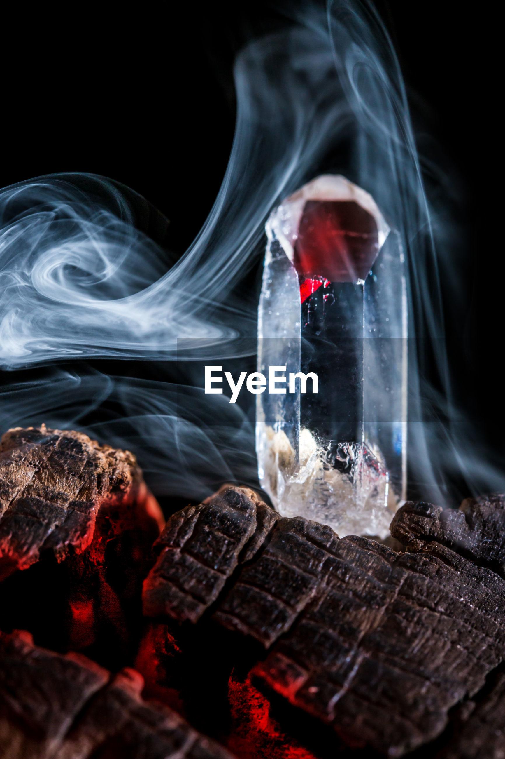 Close-up of crystal on burning wood against black background
