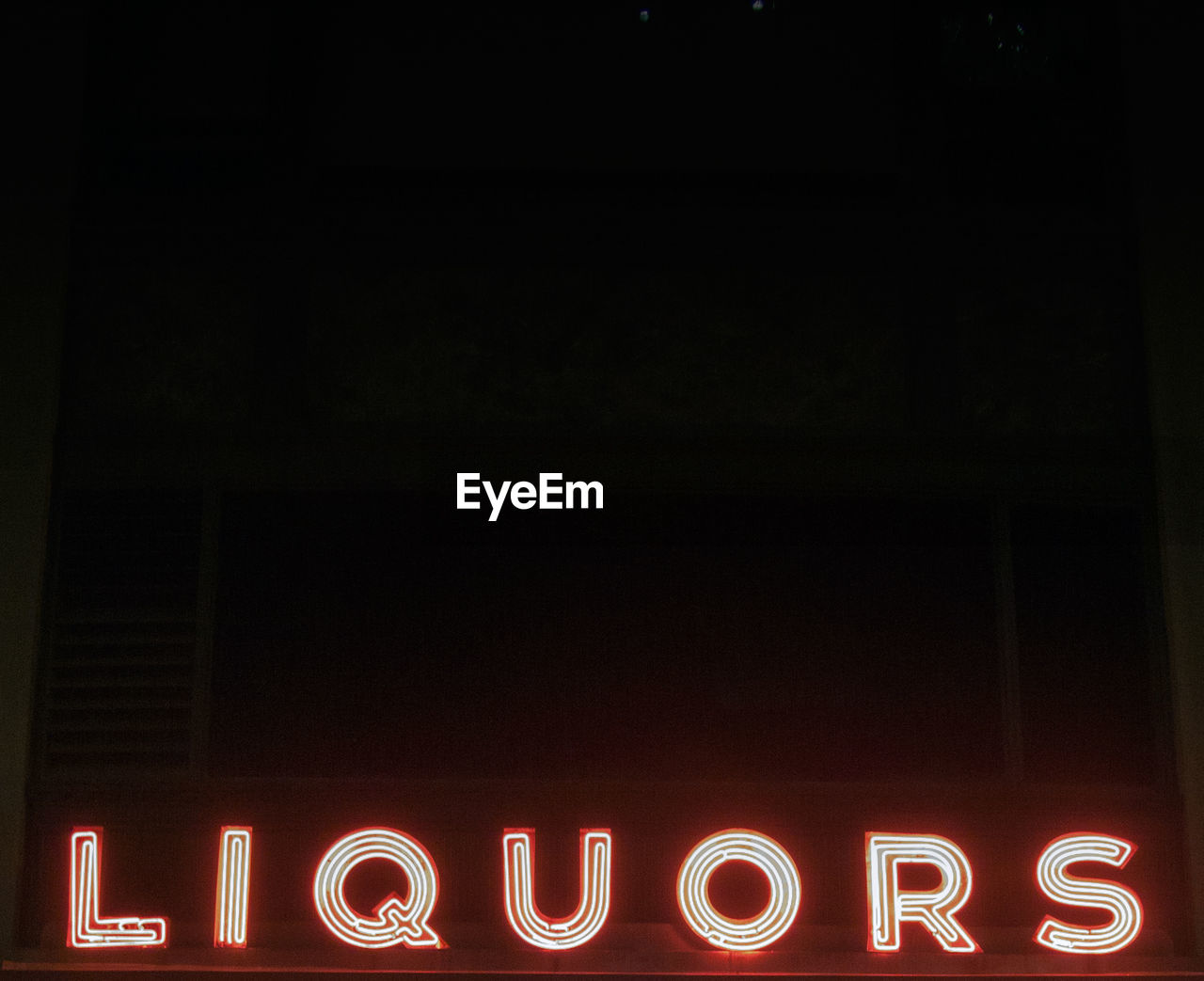 Illuminated Liquors Neon Sign Against Clear Sky At Night