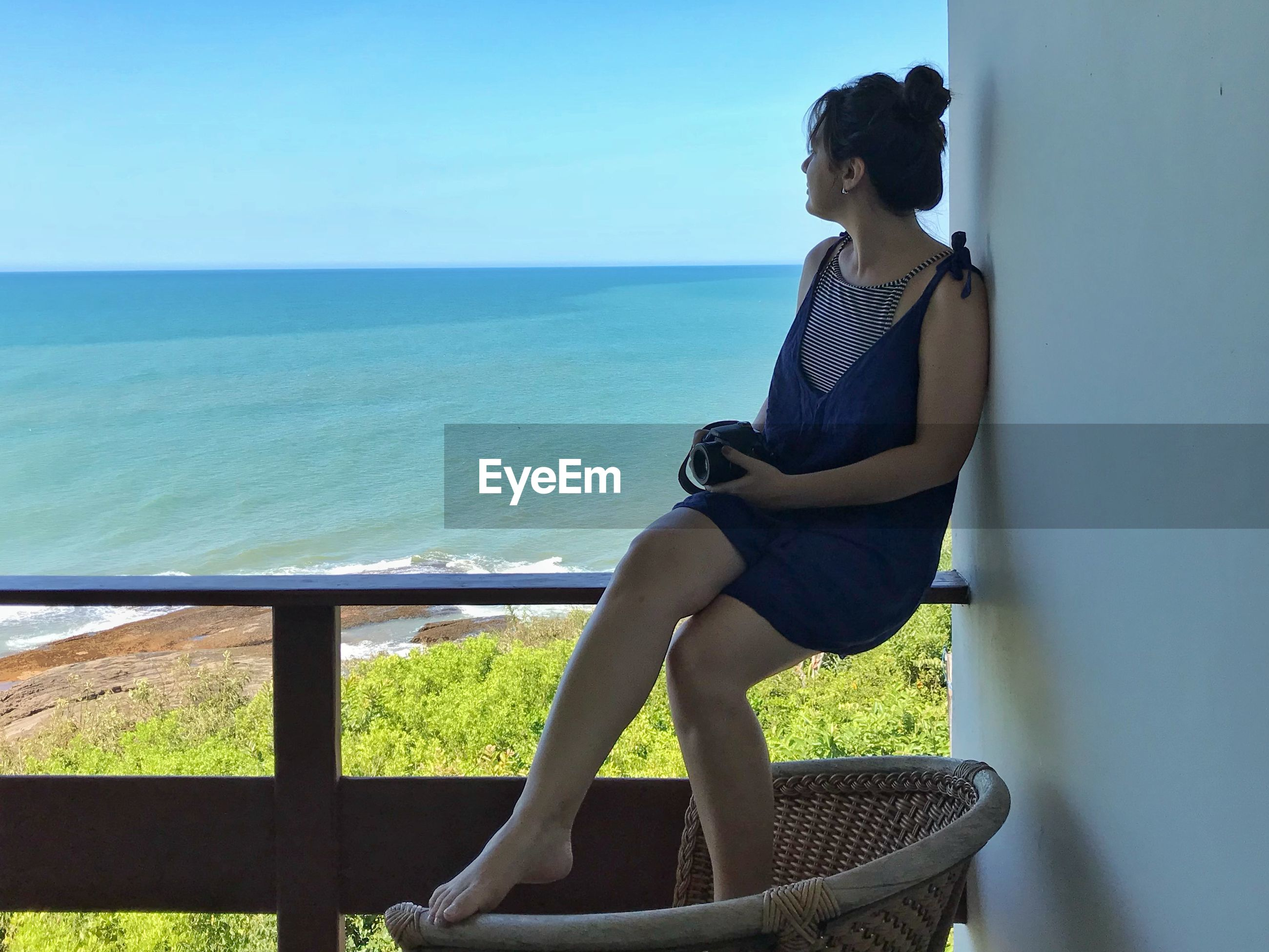woman looking at sea while sitting on balcony
