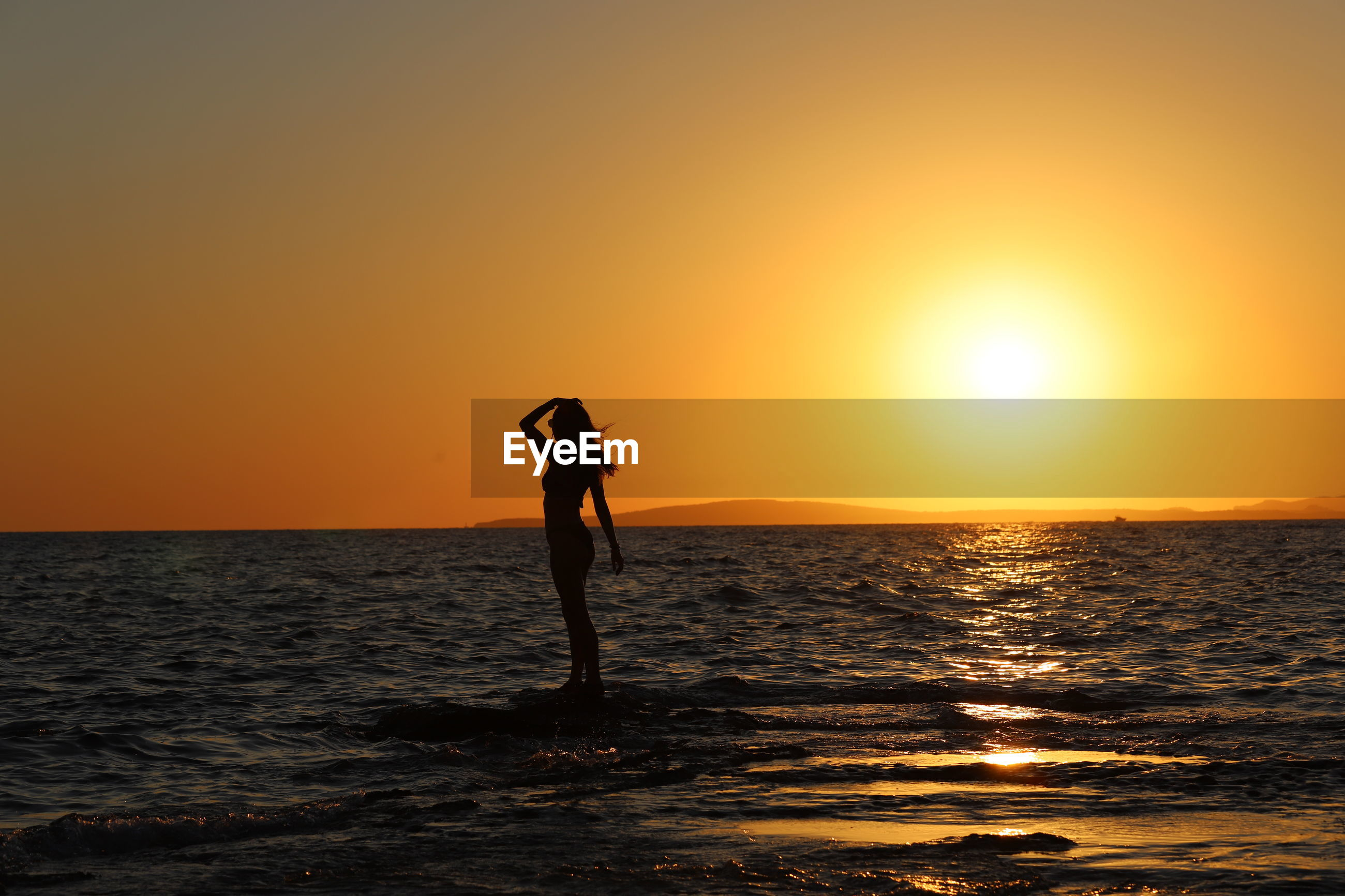 SILHOUETTE WOMAN STANDING ON SHORE AGAINST ORANGE SKY