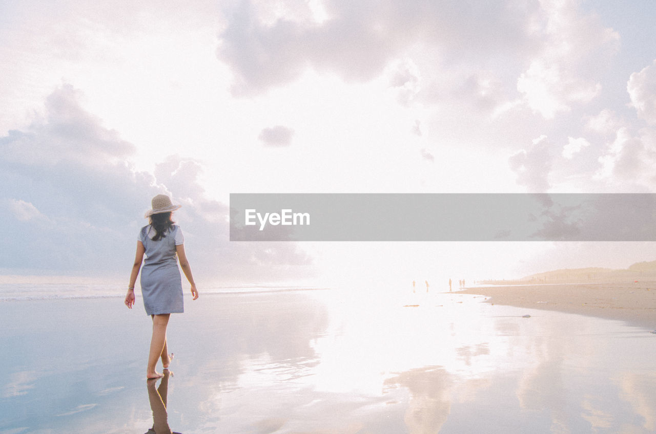 sky, water, cloud - sky, one person, leisure activity, standing, lifestyles, nature, full length, real people, women, sea, beauty in nature, tranquility, reflection, rear view, adult, scenics - nature, outdoors