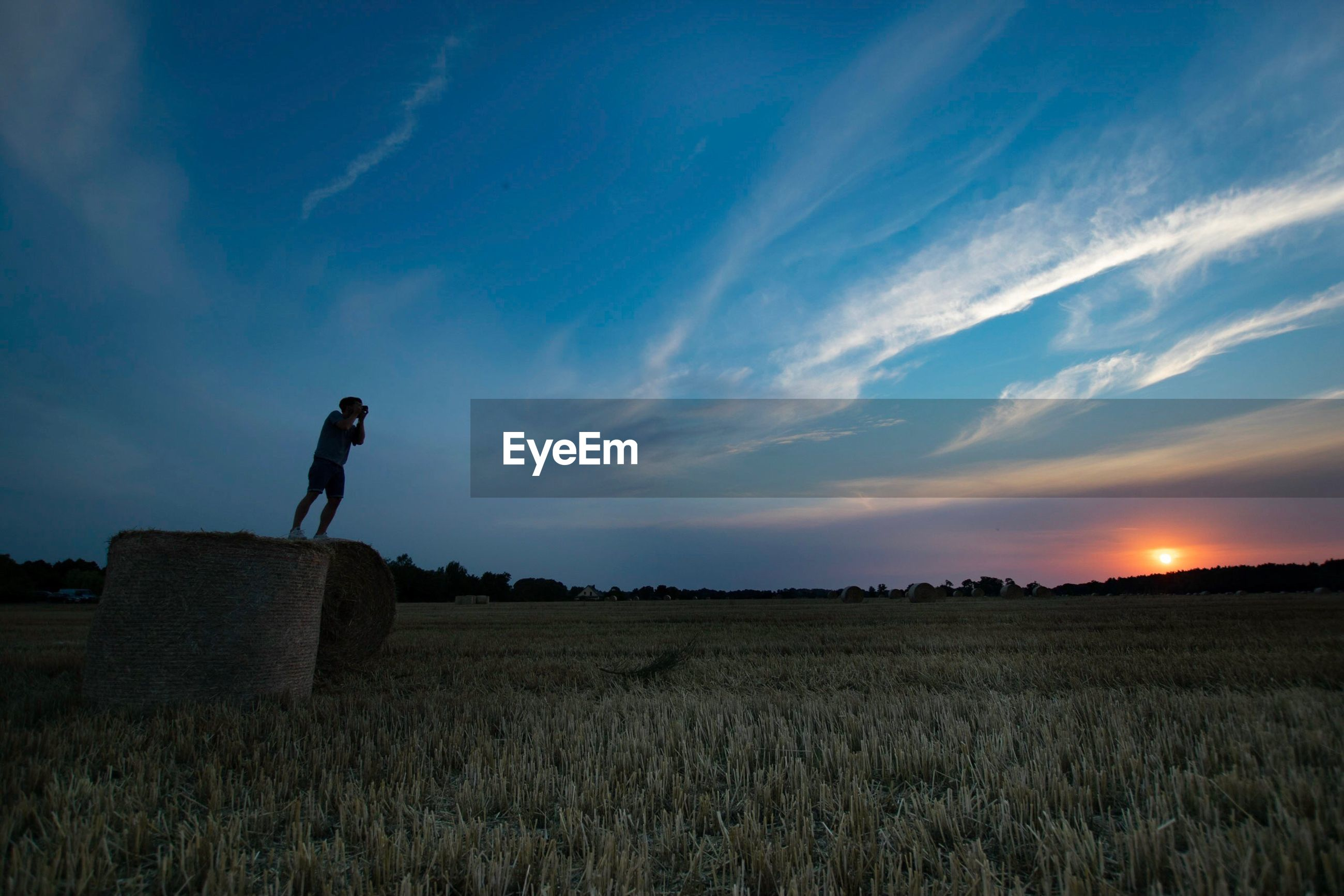 MAN STANDING ON FIELD DURING SUNSET