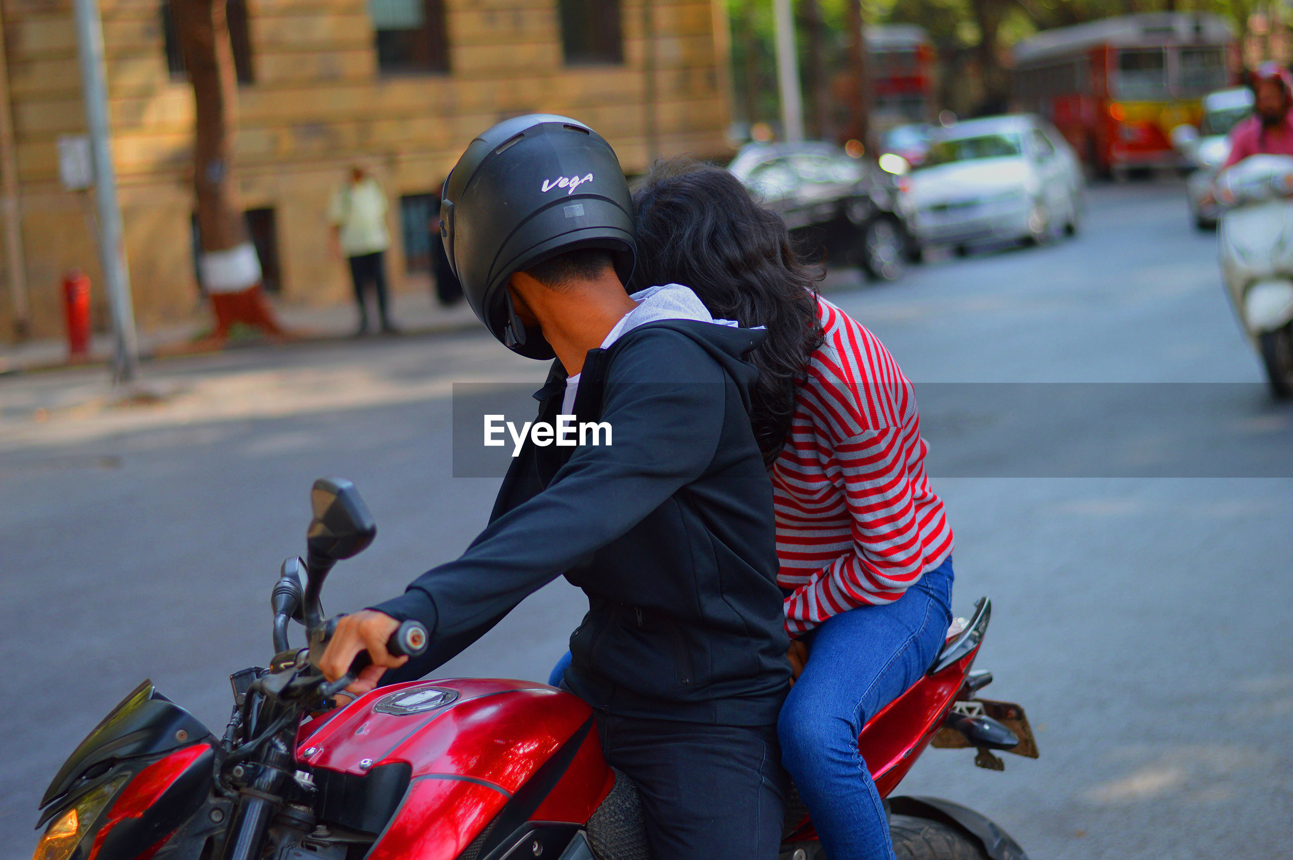 Couple sitting on motorcycle in city