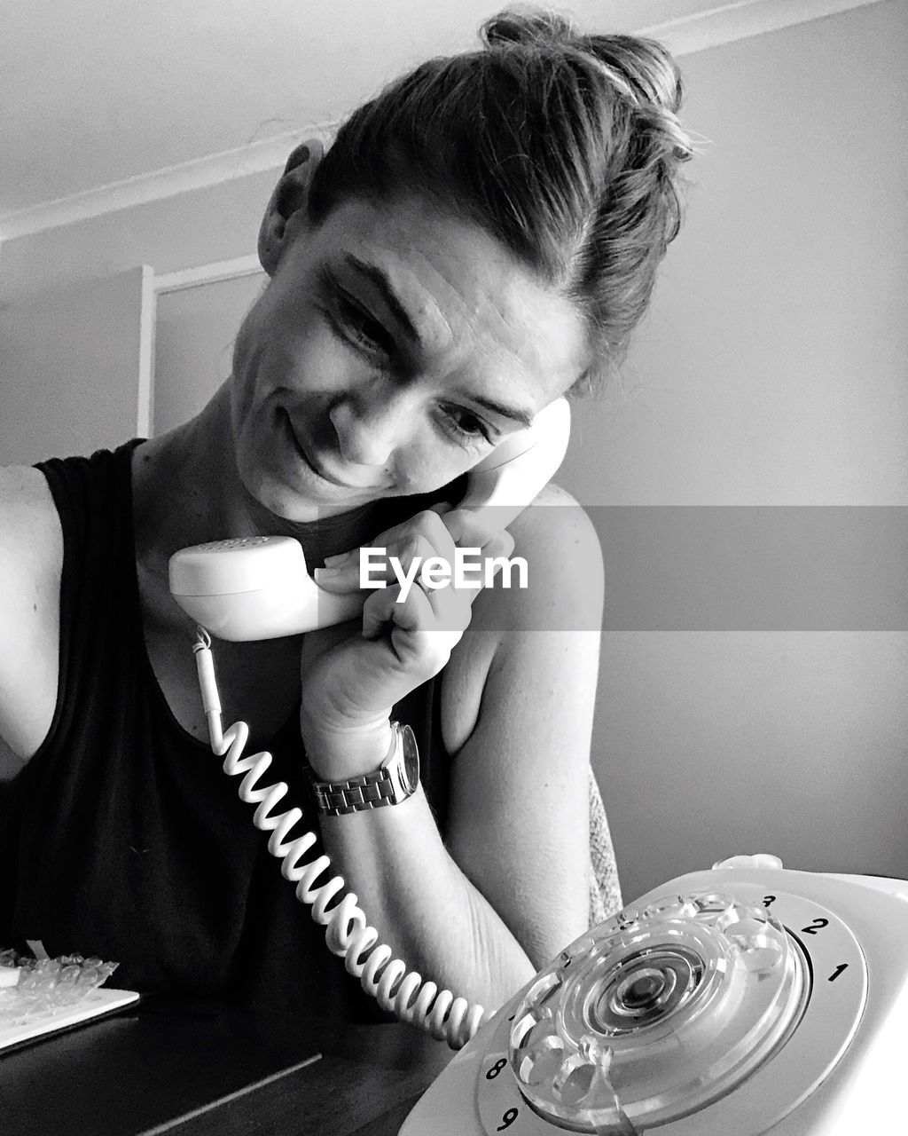 Smiling woman talking on old-fashioned rotary phone at home