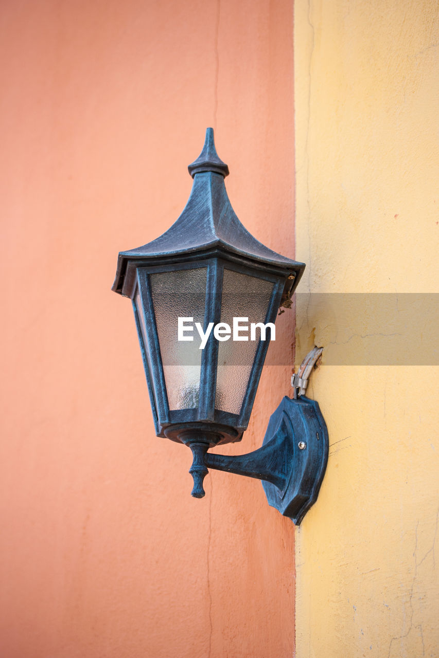wall - building feature, built structure, lighting equipment, no people, architecture, low angle view, day, wall, orange color, electric lamp, yellow, building exterior, outdoors, mounted, old, metal, connection, electricity, light fixture