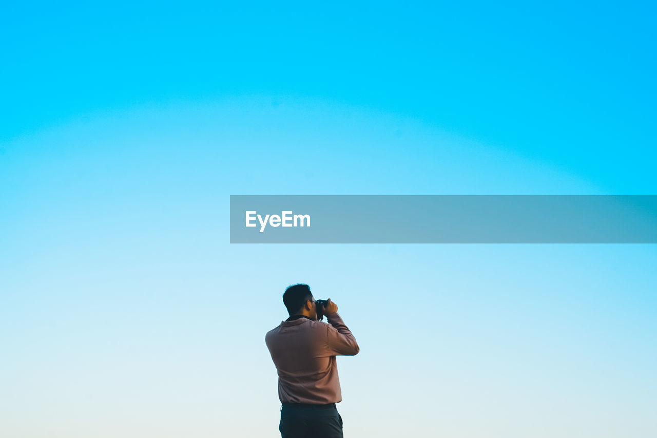 Rear view of man photographing against clear sky